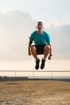 Konzentrierte männliche Athleten springen am Morgen