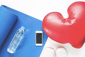 Konzept der Gesundheitsversorgung mit Sport-Ausrüstungen auf weißem Hintergrund mit Smartphone, Flat lay