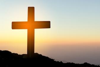 Konzept konzeptionellen gelben Kreuz Religion Symbol Silhouette in der Natur über Sonnenuntergang oder Sonnenaufgang Himmel