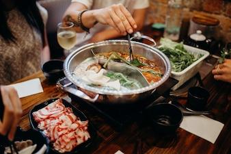 Koreanische Hot Pot Mahlzeit. Hände nehmen Essen mit Stäbchen.