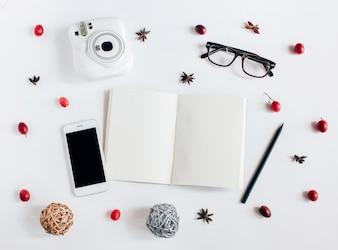 Kreativ flach legen leer Notebook, Smartphone, Instant Kamera mit Herbst Ornamente auf weißem Hintergrund, Draufsicht