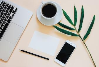 Kreative flache Laien Foto von Arbeitsbereich Schreibtisch mit Laptop, Smartphone, Kaffee und leeres Papier mit Kopie Raum Hintergrund, minimaler Stil