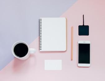 Kreative flache Laien Foto von Arbeitsbereich Schreibtisch mit leeren Notebook, Smartphone, Karte, Bleistift und heißen Kaffee mit Kopie Raum Hintergrund, minimalen Stil