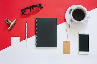 Kreative flache Laien Foto von Arbeitsbereich Schreibtisch mit Smartphone, Brillen, Kaffee, Tag und Notebook mit Kopie Raum Hintergrund, minimal gestylt