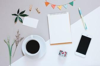 Kreative flache Laienentwurf des netten Arbeitsbereichs Schreibtisch mit Notizbuch, Kaffee, smartphone und verziertes nettes Handwerk mit Exemplarplatzhintergrund, minimaler Art