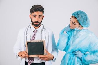 Kühles medizinisches Team posiert mit Tafel