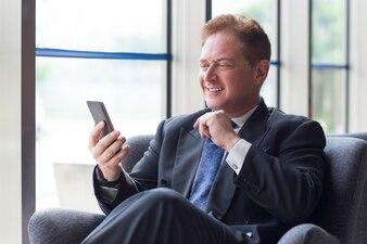 Lächelnd Geschäftsmann mit Handy in der Lobby
