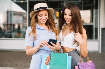 Lächelnde Frauen betrachten Smartphone-Bildschirm