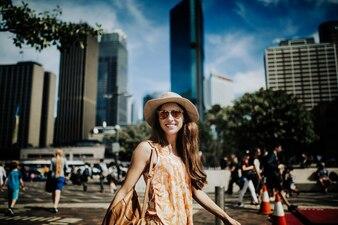 Lächelnde Gesicht Frau in Hut und Sonnenbrille Erkundung der Stadt, mit Sydney Skiline im Hintergrund.