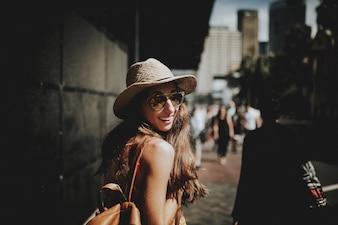 Lächelnde glückliche Frau zu Fuß in einer Sydney Straße und drehen sich um die Kamera zu betrachten.