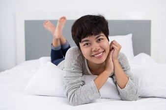 Lächelnde junge asiatische Frau ruht im Bett