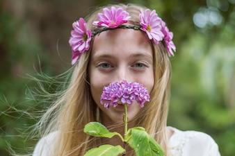 Lächelnde junge Frau, die eine Blume riecht