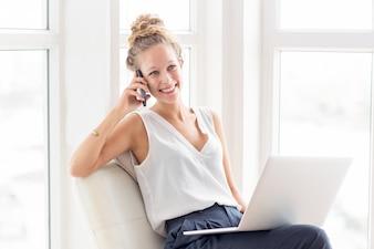 Lächelnde nette Frau, die am Telefon auf Loggia spricht