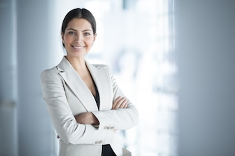 Lächelnde weibliche Geschäftsführer mit Arme gekreuzt