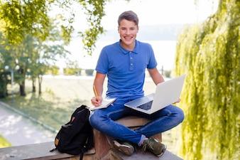 Lächelnder Junge, der mit Laptop im Park studiert