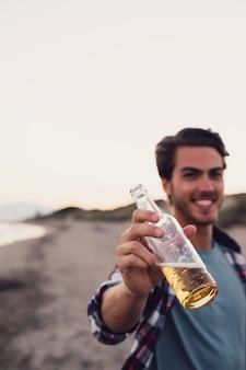 Lächelnder Kerl mit Bier am Strand