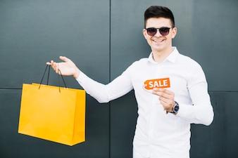 Lächelnder Kerl mit Verkaufszeichen