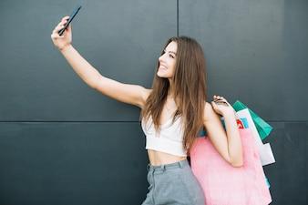 Lächelndes Mädchen mit Taschen, die selfie machen