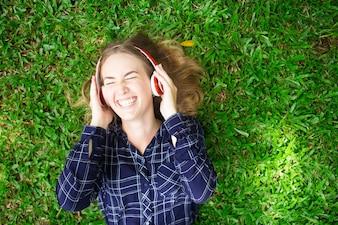 Lachendes Mädchen, das Musik auf Gras zuhört