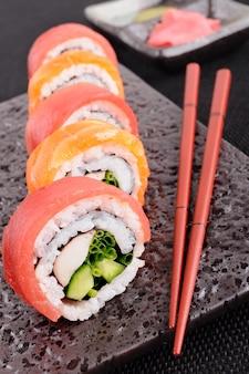 Lachs Thunfisch-Sushi-Rolle mit Stäbchen closeup