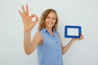 Lady Holding Bilderrahmen und zeigt OK Zeichen