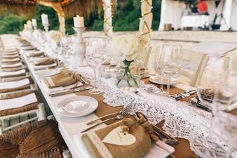 Lange weiße Tisch steht unter weißen Zelten am Sandstrand