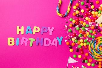 Leckere appetitliche Party-Accessoires Alles Gute zum Geburtstag auf hellem rosa Hintergrund