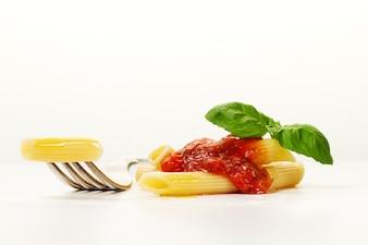 Leckere bunte appetitlich gekochte Spaghetti italienische Pasta mit Tomatensauce Bolognese und frischem Basilikum auf Gabel. Kreative Portion, Nahaufnahme.