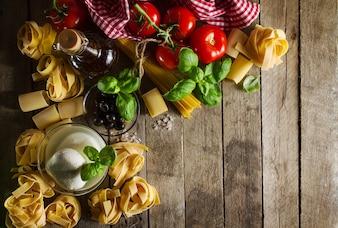 Leckere bunte frische italienische Lebensmittel-Konzept mit verschiedenen Pasta Spaghetti, Käse Mozzarella, frischen Basilikum, Tomaten, Olivenöl, Gewürze. Draufsicht. Kochen Konzept. Platz für Text.