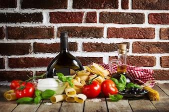 Leckere bunte frische italienische Lebensmittel-Konzept mit verschiedenen Pasta Spaghetti, Käse Mozzarella, frischen Basilikum, Tomaten, Olivenöl, Gewürze. Kochen Konzept. Platz für Text.