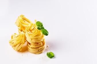 Leckere frische bunte Zutaten zum Kochen Pasta Tagliatelle mit frischem Basilikum und Tomaten. Heller Hintergrund.