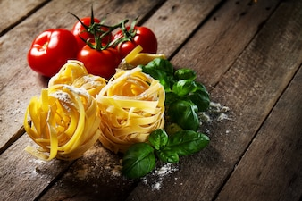 Leckere frische bunte Zutaten zum Kochen Pasta Tagliatelle mit frischem Basilikum und Tomaten. Horizontal. Holztisch Hintergrund.