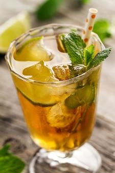 Leckere frische erfrischende Sommertee trinken mit Eis, kalten Tee, Kalk und Minze in Glas auf Holzuntergrund. Nahansicht.