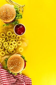 Leckere frische ungesunde Hamburger mit Ketchup und Gemüse und Chips auf gelb lebendigen hellen Hintergrund. Draufsicht mit Kopierraum.