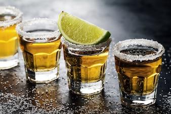 Leckerer Alkohol trinken Cocktail Tequila mit Kalk und Salz auf lebendigen dunklen Hintergrund. Nahansicht. Horizontal.