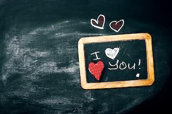 Liebe oder Valentinstag-Konzept mit Tafel und Herzen auf