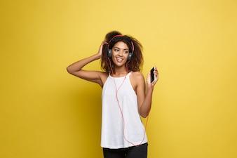Lifestyle-Konzept - Porträt der schönen African American Frau freudig Musik hören auf Handy. Gelbe Pastell Studio Hintergrund. Text kopieren