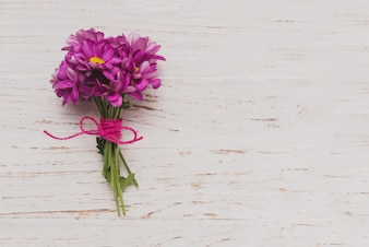 Lila Blüten auf weißem Holz-Oberfläche gebunden