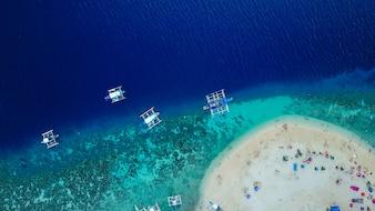 Luftaufnahme der Sandstrand mit Touristen Schwimmen in schönen klaren Meerwasser der Sumilon Insel Strand Landung in der Nähe von Oslob, Cebu, Philippinen. - Farbverarbeitung steigern