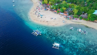 Luftaufnahme der Sandstrand mit Touristen Schwimmen in wunderschönen klaren Meerwasser der Sumilon Insel Strand Landung in der Nähe von Oslob, Cebu, Philippinen. - Farbverarbeitung verstärken.