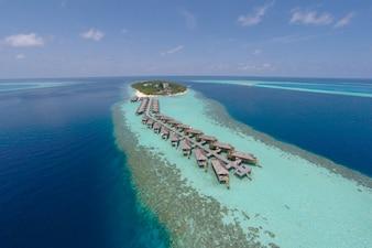 Luftaufnahme einer tropischen Insel im türkisfarbenen Wasser. Luxuriöse Überwasser-Villen auf tropischen Insel Resort Malediven für Urlaub Urlaub Hintergrund Konzept -Boost up Farbe Verarbeitung.