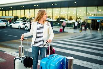 Mädchen in weißer Jacke steht auf Kreuzung mit blauen und weißen Koffern