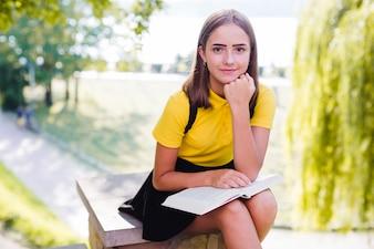 Mädchen mit Buch, das Kamera betrachtet