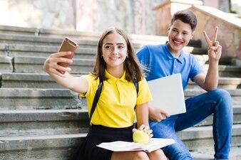 Mädchen mit dem Jungen, der selfie macht