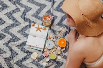 Mädchen mit Hut und Agenda auf Strandtuch