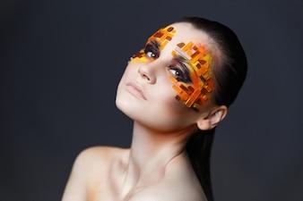 Mädchen mit orange und roten Strasssteinen auf ihrem Gesicht.