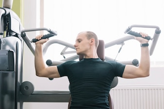Man Training mit Simulator im Fitness-Studio
