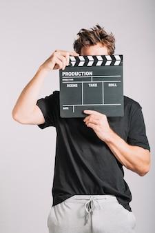 Man versteckt sein Gesicht hinter Filmklappe