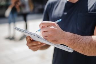 Mann hält Notizbuch schreiben