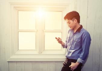 Mann mit einem Handy in einem Fenster